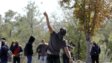 A demonstrator throws a stone at anti-riot police during clashed outside of the Middle Eastern Technical University (METU) in Ankara.
