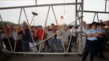 Picketers push up against a fence holding them out of Swanson Dock, Melbourne. April 8, 1998.