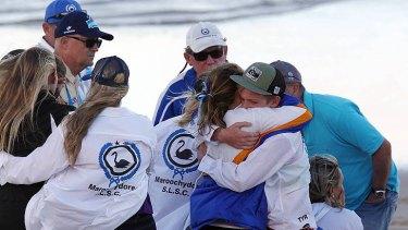 Maroochydore Surf Life Saving club members embrace.