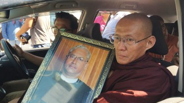 A Buddhist monk holds a portrait of Ko Ni on the way to his funeral.