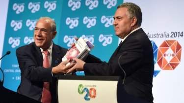 Treasurer Joe Hockey holds up a report with OECD secretary-general Angel Gurria (L) at the G20 Finance Ministers and Central Bank Governors Meeting in Cairns.