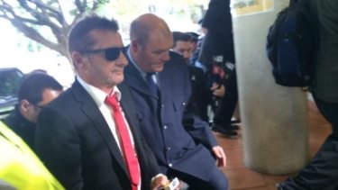 Phil Rudd arrives at court and pleads guilty to threatening a former security guard.