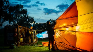 Early morning hot air balloon pilots prepare for take off.