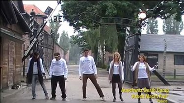 Dancing at Auschwitz in front of the 'Arbeit macht frei' (work sets you free') sign.