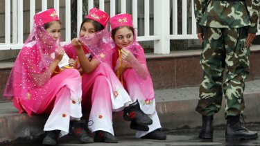 Cheerleaders wait for the start of the Xinjiang leg of the Olympic torch relay in the regional capital Urumqi. Heavy security was in place, with police restricting movement in the city.PICTURE: REUTERS