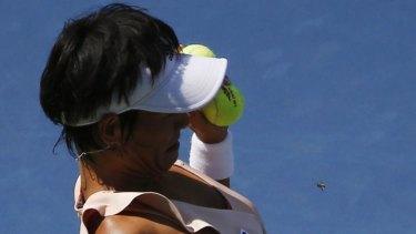 Kimiko Date-Krumm avoids a bee before serving.