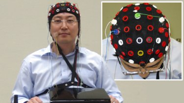 A researcher wearing a cap that can read brain signals rides on a wheelchair that can be steered by detecting brain waves at Riken Brain Science Institute in Wako near Tokyo, Japan.