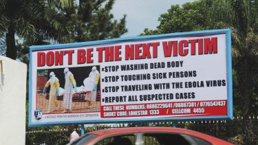 A car drives past a public health advertisement against the Ebola virus in Monrovia.