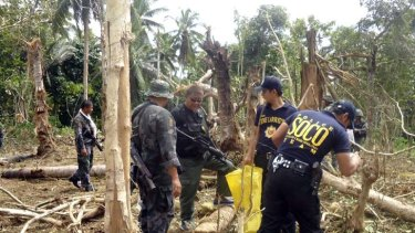 Philippine National Police Special Action Forces and SOCO (Scene of the Crime Operatives) investigators examine the site on the island province of Jolo in southern Philippines.