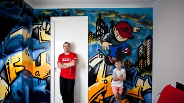 Commercial graffiti artist Ashley Goudie, left, and Oscar Greenshields, 10, with the skater boy Goudie painted in Oscar's bedroom at Eynesbury, west of Melbourne. Oscar's name is painted in street style at left.