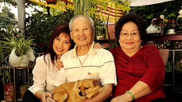 Julie Huynh with her father Minh Huynh, mother De Chung and their dog Simba at the parents' home in Northcote.
