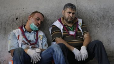 Exhausted Palestinian medics take a break after carrying wounded people injured from the Israeli strike in the Shujaiyah neighbourhood, into the emergency room at Gaza City's Shifa Hospital.