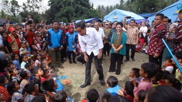 Indonesian President Joko Widodo, center, talks to children who were evacuated from their homes.