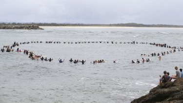Vale Zac Young: Friends of the teenage shark attack victim form a circle off Port Macquarie's Town Beach to remember him.