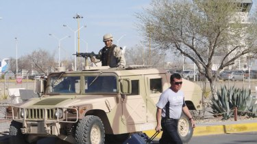 A stranded passenger at the Ciudad Juarez airport passes a security checkpoint after a bomb threat closes the airport.