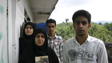 The Hashimi family: (from left) daughter Zahra, mother Nahle Abd Uan, and sons Qasseme and Hossein. Nahle holds a picture of her husband.