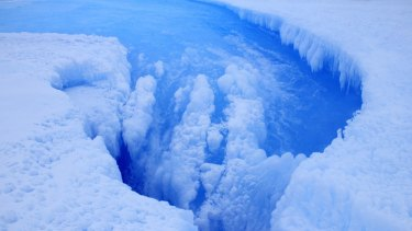 Moulin inside the crater on the Roi Baudouin ice shelf showing the drainage of meltwater.