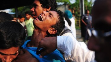 A Bangladeshi youth reacts after finding a relative among the dead.