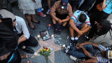 Fans of  Michael Jackson sit around the singer's star on the Hollywood Walk of Fame in Los Angeles.