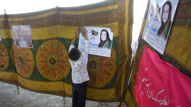 An Afghan boy pins up an election poster of presidential candidate Shahla Atta in Kabul.