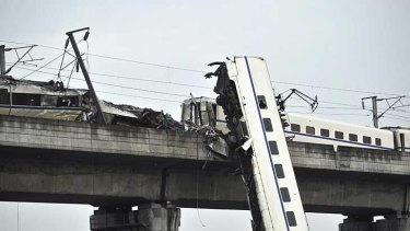A man sits by the wreckage of a train accident in Wenzhou, in eastern China.