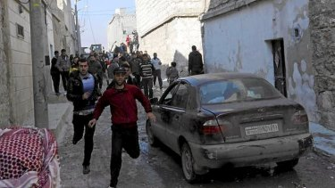 Residents flee an air strike by a fighter jet loyal to Syrian President Bashar al-Assad in Aleppo's al-Marja district on Monday. An Australian has been reportedly killed in the ongoing civil war.