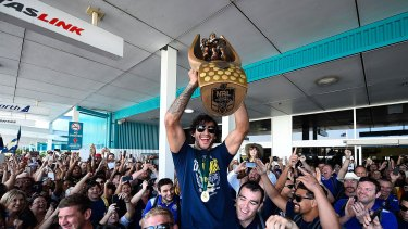 Johnathan Thurston of the Cowboys is hoisted onto the shoulders of Ben Hannant and Kane Linnett with the NRL trophy after arriving back at Townsville airport.