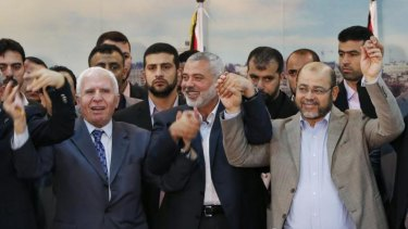 Together after seven-year split ... senior Fatah and Hamas leaders hold their hands after announcing a reconciliation agreement in Gaza City.