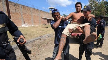 Police carry an injured inmate out of the National Prison compound in Comayagua, Honduras.