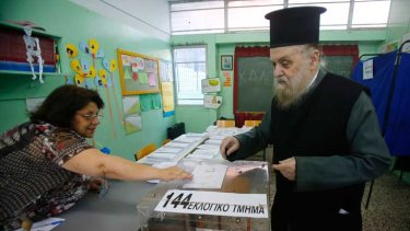A Greek Orthodox priest casts his ballot at an Athens primary school used as a polling station.