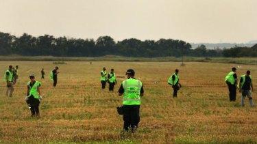 Investigators search the MH17 crash site.