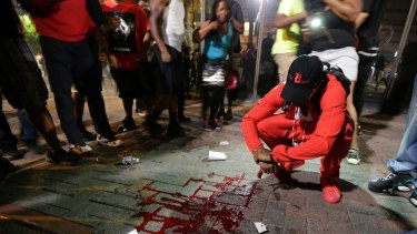 A man squats near a pool of blood after a man was shot during a protest in Charlotte.