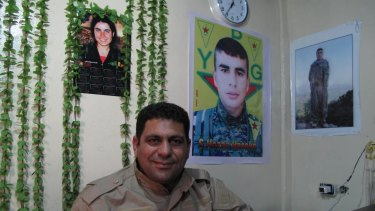 Hamid Derik, who is training new conscripts to Rojava's army, sits under a picture of 22-year-old Arin Mirkan, who ran into a group of Islamic State soldiers and blew herself up.