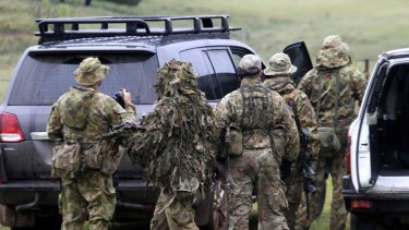 Ready for the hunt ... a specialist police group dressed in camouflage preparing to leave Nowendoc yesterday to search for Malcolm Naden.