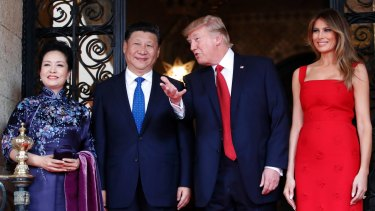 President Donald Trump talks with Chinese President Xi Jinping, with their wives, first lady Melania Trump and Chinese first lady Peng Liyuan as they pose for photographers before dinner at Mar-a-Lago.