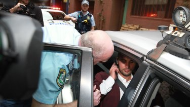 A police officer asks Salim Mehajer to leave a taxi outside Sydney City police station on April 2.