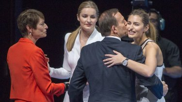 Got his back: Tony Abbott plants one on daughter Frances at the Coalition's campaign launch, as wife Margie and the couples other daughter Bridget look on.