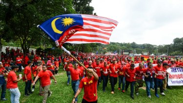 The protesters march behind the Malaysian flag. Their emphasis on Malay rights has aroused concern in the multi-ethnic nation.