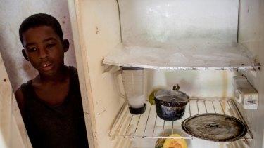 Joffren Polanco stands beside his almost empty fridge in Caracas.