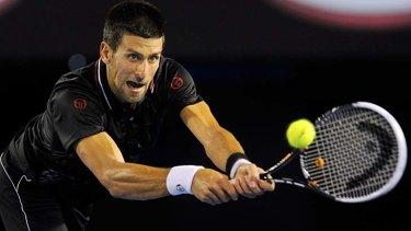 Novak Djokovic at full stretch as he plays a backhand.