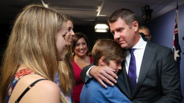 Mr Baird embraces his family after announcing his resignation.