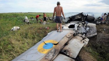 A man stands on the wreckage of a Ukrainian AN-26 military transport plane after it was shot down by a missile in the village of Davydo-Mykilske, east of Lugansk near the Russian border.