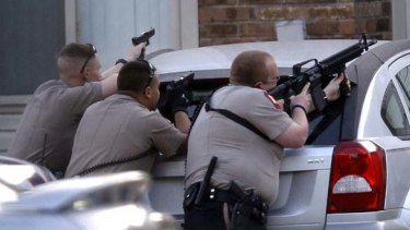 Police aim their guns at an apartment where the suspect was believed to be hiding.