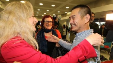 Friends greet Chinese-Australian artist Guo Jian as he arrives at Syndey airport after being deported from from China.