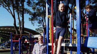 Doug Garske, fund-raising vice-president of Lane Cove West P&C with his daughter Tyler and student  Gabriel Lucarelli using the playground the P&C funded.