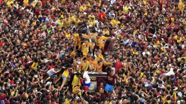 Catholic devotees try to touch the statue of the Black Nazarene as it is pulled on a carriage during an annual procession in Manila last week. More than a million barefoot believers joined the procession, which left two dead and more than 1000 injured.