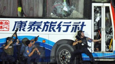 Policemen take position as they start their attack on the hijacked tourist bus.