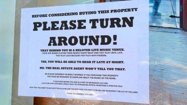 Sign taped to the for sale sign of a house near the live music venue the Retreat Hotel in Brunswick.