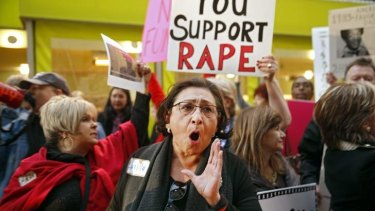 """Protester Lucilla Tenorio shouts """"Skip the show"""" to ticket-holders attending a Bill Cosby show in Denver on Saturday."""