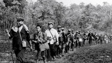 Khmer Rouge leader Pol Pot, who turned Cambodia into a vast killing field and slave labour camp, leads a column of his men.